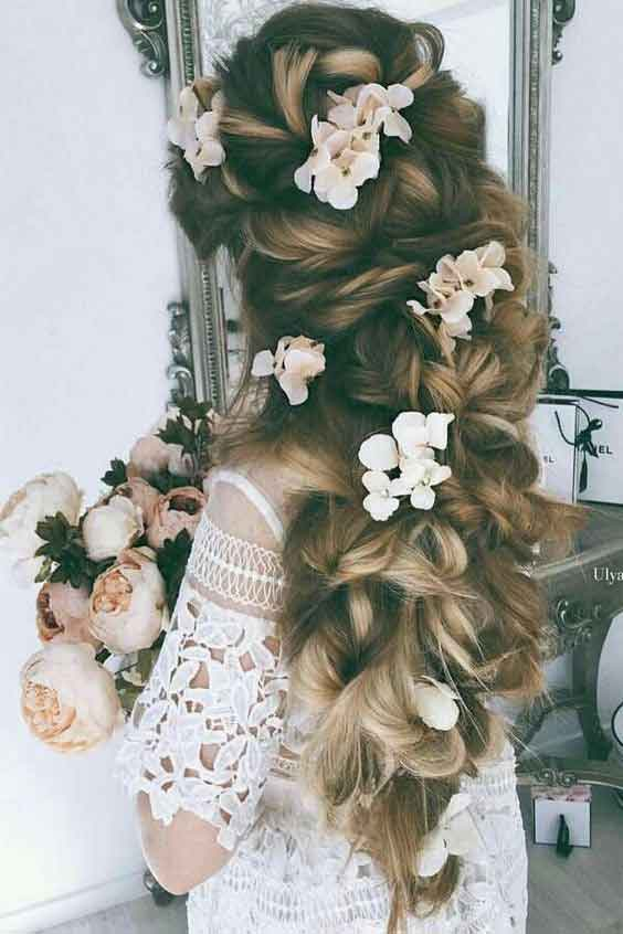 Loose twisted braid with flower hairstyle for engagement brides